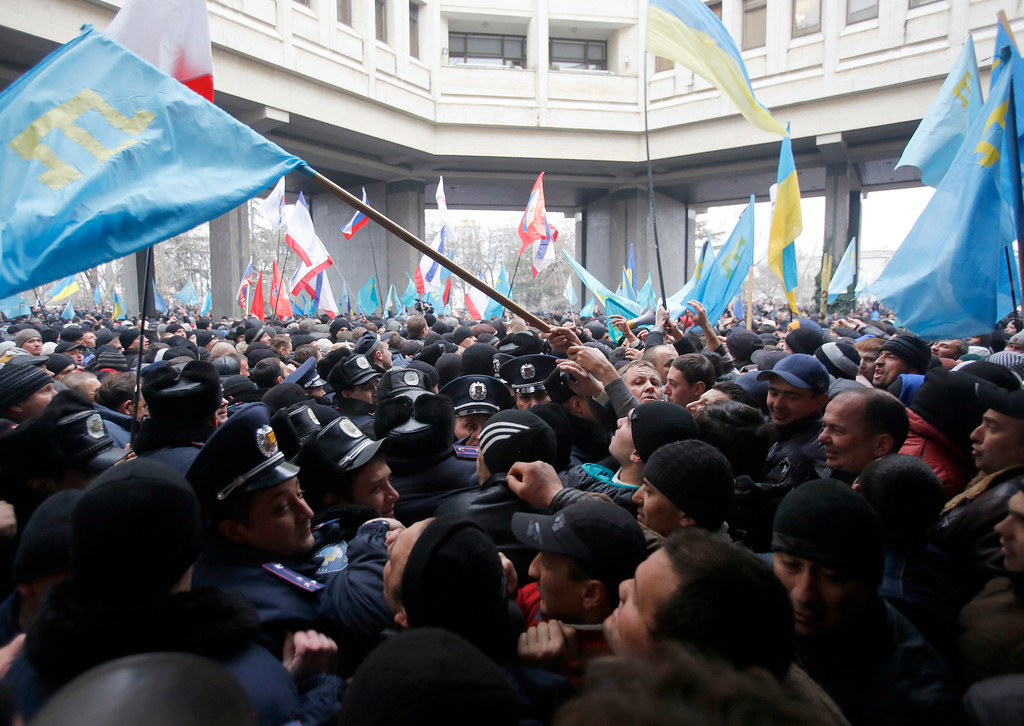 . Crimean Tatars, right clash with police in front of a local government building in Simferopol, Crimea, Ukraine, Wednesday, Feb. 26, 2014. More than 10,000 Muslim Tatars rallied in support of the interim government. That group clashed with a smaller pro-Russian rally nearby. Fistfights broke out between pro- and anti-Russian demonstrators in Ukraine\'s strategic Crimea region on Wednesday as Russian President Vladimir Putin ordered massive military exercises just across the border. (AP Photo/Darko Vojinovic)