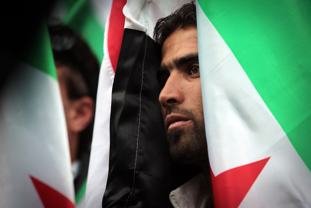 . A Syrian immigrant who lives in Bulgaria observes minute of silence during demonstration in front of the European Commission Representation office in Sofia, Bulgaria, Saturday, Aug. 31, 2013. (AP Photo/Valentina Petrova)