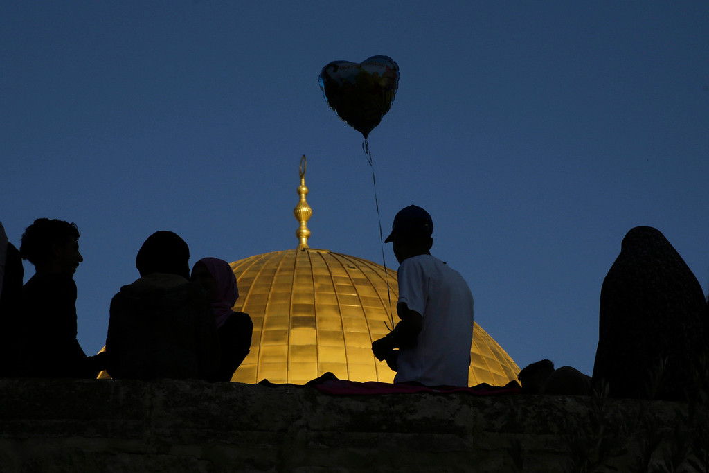 . A Palestinian boy hold a balloon in front of the Dome of the Rock shrine in Jerusalem, Friday, June 15, 2018 during the traditional morning prayer of the Muslim holiday of Eid al-Fitr. (AP Photo/Mahmoud Illean)