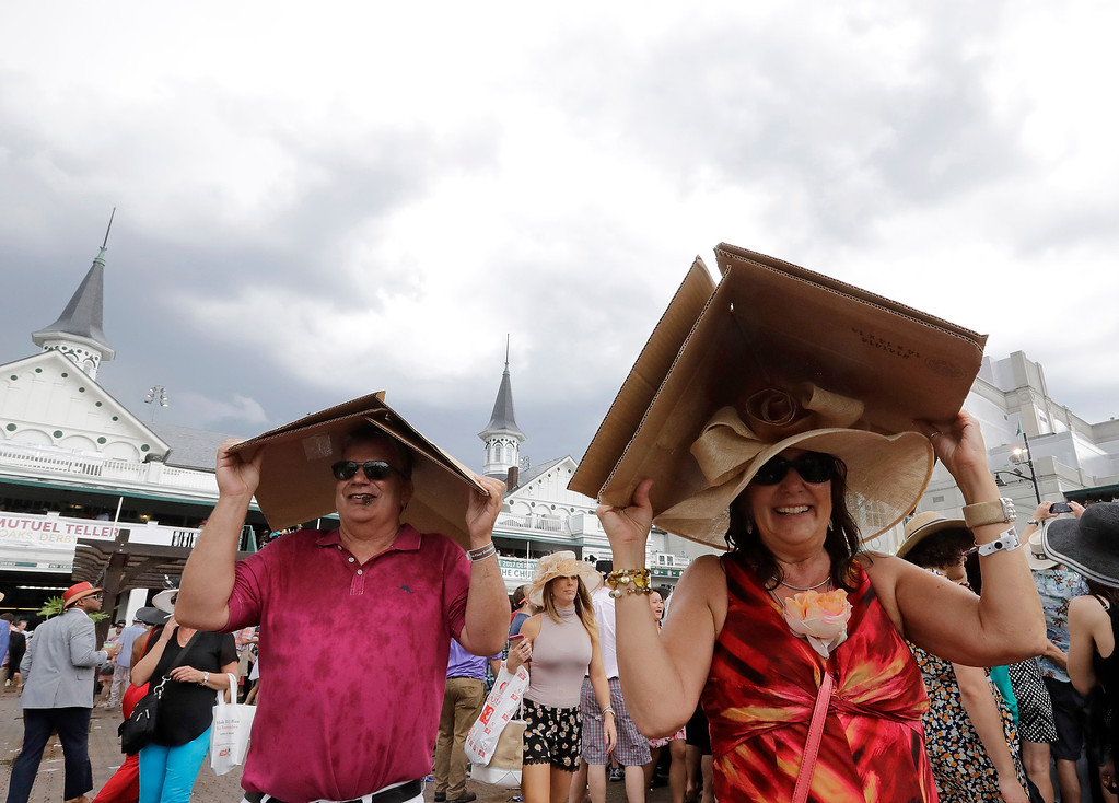 . Scott and Christine Price cover themselves from some rain before the 142nd running of the Kentucky Derby horse race at Churchill Downs Saturday, May 7, 2016, in Louisville, Ky. (AP Photo/Morry Gash)