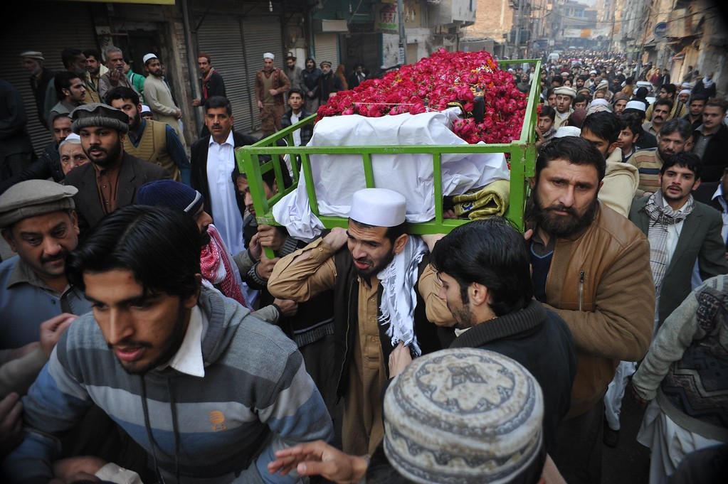 . Pakistani mourners carry a coffin during a funeral ceremony a day after an attack on an army-run school by Taliban militants in Peshawar on December 17, 2014.  Pakistan began three days of mourning on December 17 for the 132 schoolchildren and nine staff killed by the Taliban in the country\'s deadliest ever terror attack as the world united in a chorus of revulsion.  AFP PHOTO / HASHAM  AHMED/AFP/Getty Images