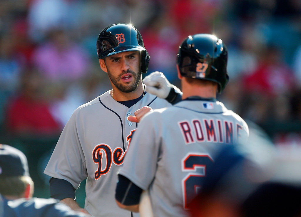 . Detroit Tigers\' J.D. Martinez, left, is congratulated by Andrew Romine after scoring on a sacrifice fly by James McCann during the second inning of a baseball game against the Los Angeles Angels, Sunday, May 31, 2015, in Anaheim, Calif. (AP Photo/Mark J. Terrill)