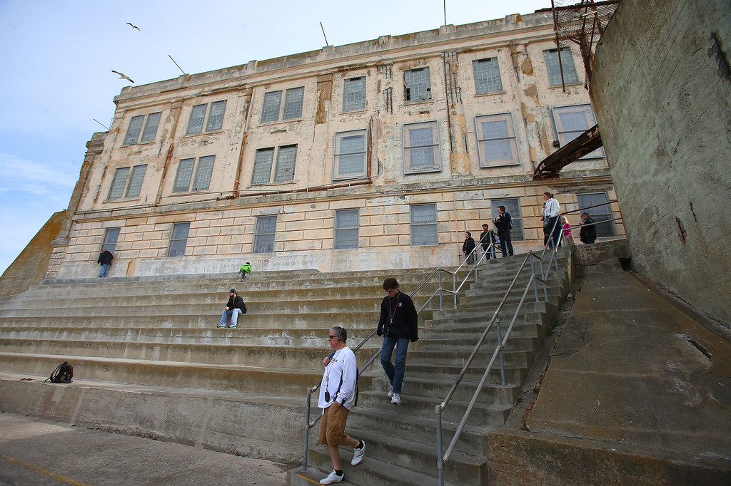 . Tourists make their way from the cellhouse out into the recreation yard on Alcatraz Island on Monday, March 18, 2013 in San Francisco, Calif.   The federal prison on the island closed 50 years ago and is now a tourist destination.  (Aric Crabb/Staff)