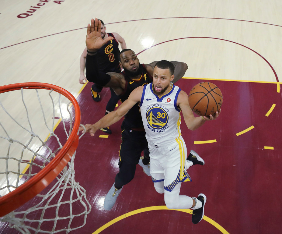 . Golden State Warriors\' Stephen Curry shoots next to Cleveland Cavaliers\' LeBron James during the second half of Game 3 of basketball\'s NBA Finals, Wednesday, June 6, 2018, in Cleveland. The Warriors defeated the Cavaliers 110-102 to take a 3-0 lead in the series. (Gregory Shamus/Pool Photo via AP)
