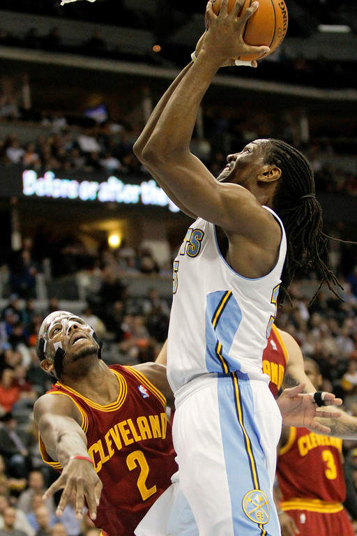 . Denver Nuggets\' Kenneth Faried, right, shoots over Cleveland Cavaliers\' Kyrie Irving, left, during the first quarter of an NBA basketball game Friday, Jan. 11, 2013, in Denver. (AP Photo/Barry Gutierrez)