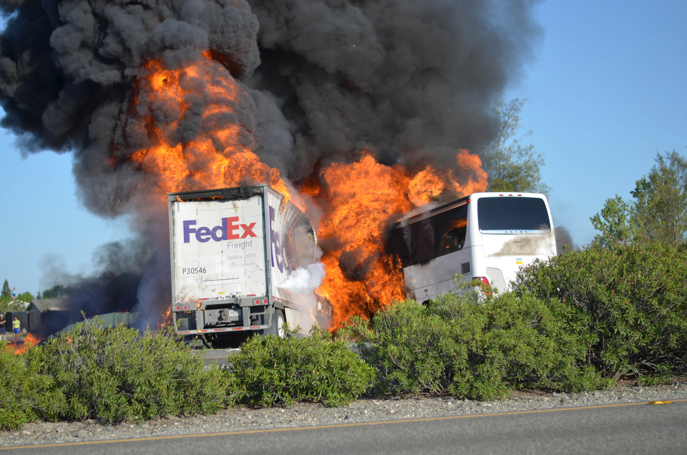 . Massive flames engulf a tractor-trailer and a tour bus just after they collide on Interstate 5, Thursday April, 10, 2014, near Orland, Calif. At least 10 people were killed in the crash, authorities said. (AP Photo/Jeremy Lockett)