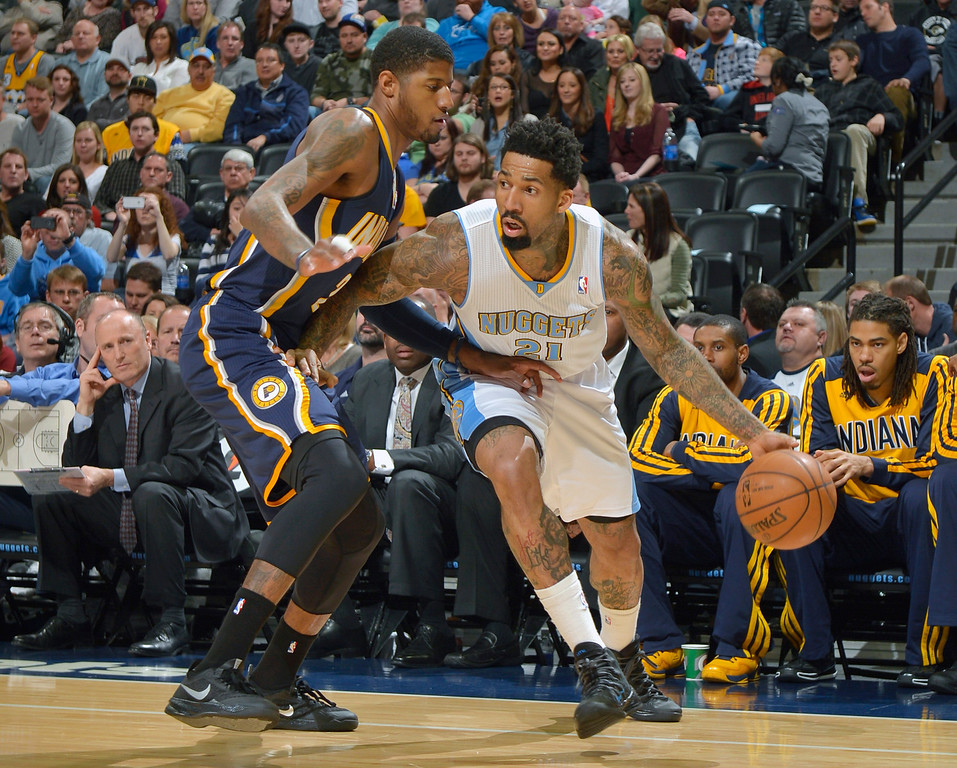 . Denver Nuggets small forward Wilson Chandler (21) moves around Indiana Pacers small forward Paul George (24) during the first quarter of an NBA basketball game Saturday, Jan. 25, 2014, in Denver. (AP Photo/Jack Dempsey)
