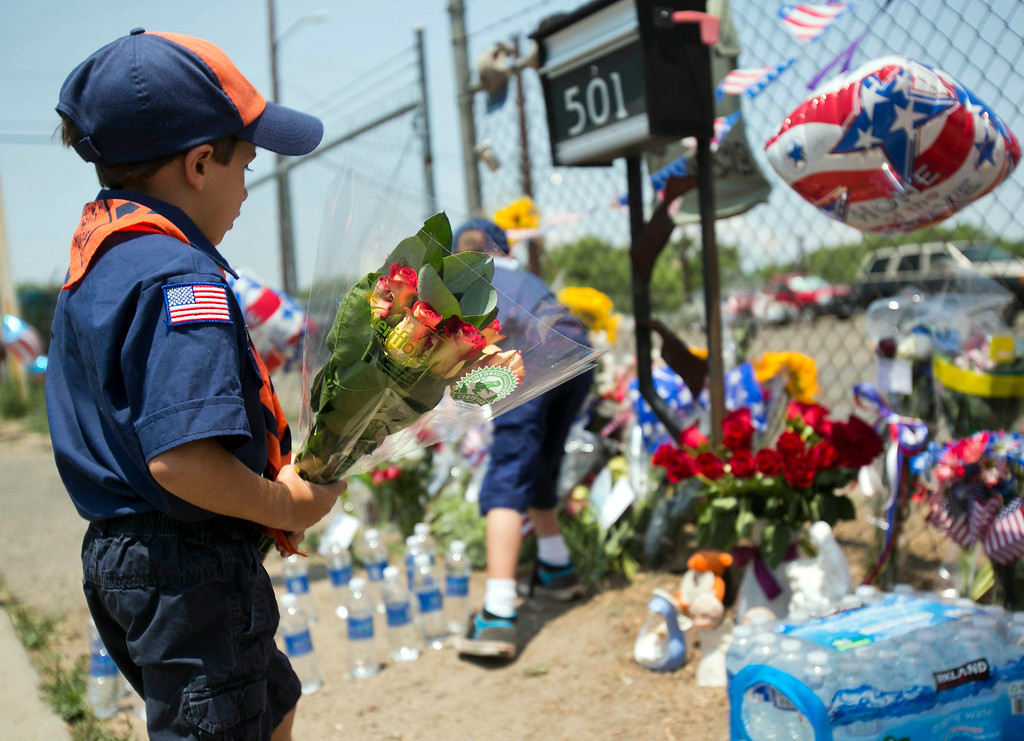 . Adam Higgins, left, and his brother Noah place flowers at a makeshift memorial at the fire station Monday, July 1, 2013, in Prescott, Ariz., where the elite team of firefighters was based.  AP Photo/The Arizona Republic, Patrick Breen)
