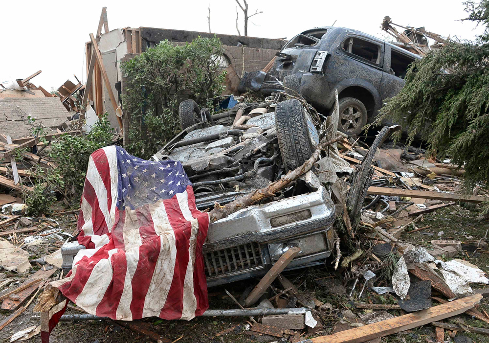 . An American flag lies on top of an overturned car after a tornado struck Moore, Oklahoma, May 20, 2013. A 2-mile-wide (3-km-wide) tornado tore through the Oklahoma City suburb of Moore on Monday, killing at least 51 people while destroying entire tracts of homes, piling cars atop one another, and trapping two dozen school children beneath rubble. REUTERS/Gene Blevins