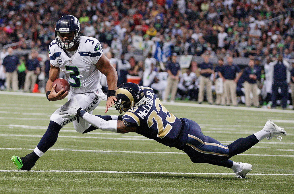 . St. Louis Rams free safety Rodney McLeod (23) tackles as Seattle Seahawks quarterback Russell Wilson (3) as Wilson rushes toward the end zone during the first half of an NFL football game, Monday, Oct. 28, 2013, in St. Louis. (AP Photo/Tom Gannam)
