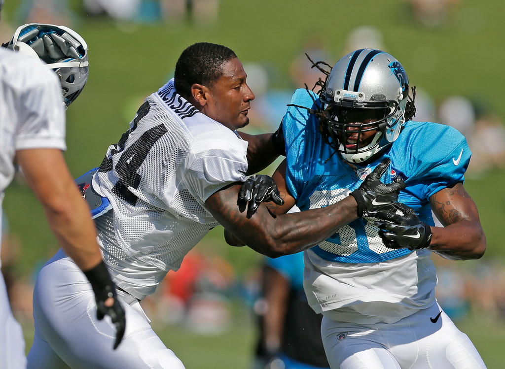 . Carolina Panthers\' Robert Lester (38)  knocks the helmet off teammate Kony Ealy (94) during an NFL football practice at their training camp in Spartanburg, S.C., Tuesday, July 29, 2014. (AP Photo/Chuck Burton)