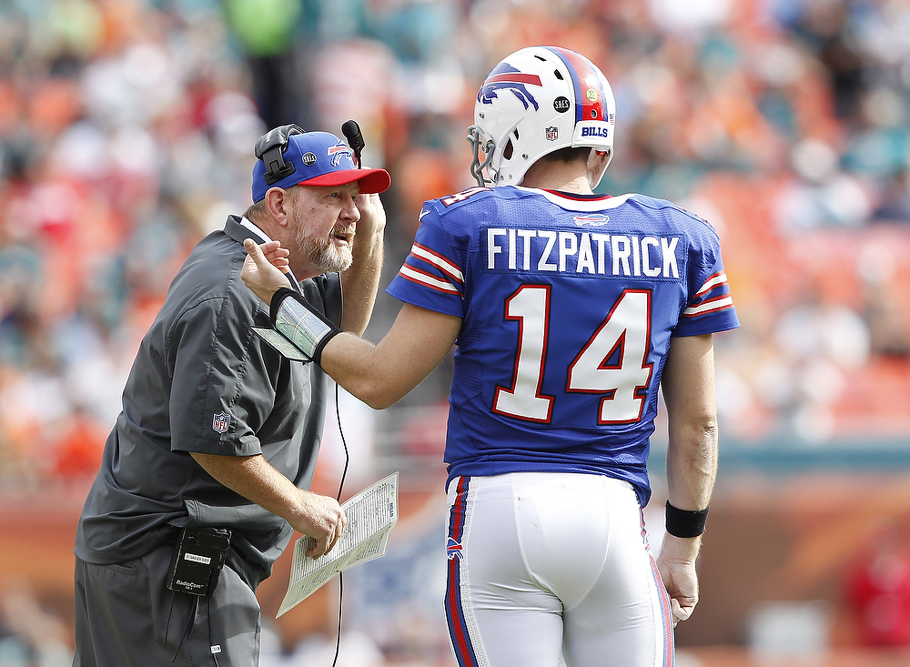 . Head coach Chan Gailey talks to Ryan Fitzpatrick #14 of the Buffalo Bills during a time out against the Miami Dolphins on December 23, 2012 at Sun Life Stadium in Miami Gardens, Florida. (Photo by Joel Auerbach/Getty Images)