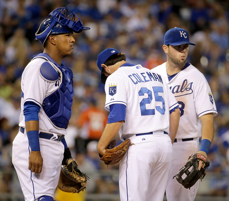. Kansas City Royals catcher Salvador Perez, relief pitcher Casey Coleman (25) and third baseman Mike Moustakas meet at the mound before Coleman was pulled from the baseball game during the fifth inning against the Detroit Tigers on Friday, Sept. 19, 2014, in Kansas City, Mo. (AP Photo/Charlie Riedel)