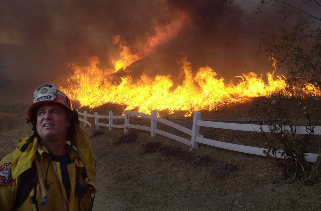 . VAL VERDE FIRE--A firefighter looks for an incomming helicopter to make a drop on a burning hillside near homes along San Martinez Grande road Friday afternoon.    10.24.03   Photo by David Crane/Daily News