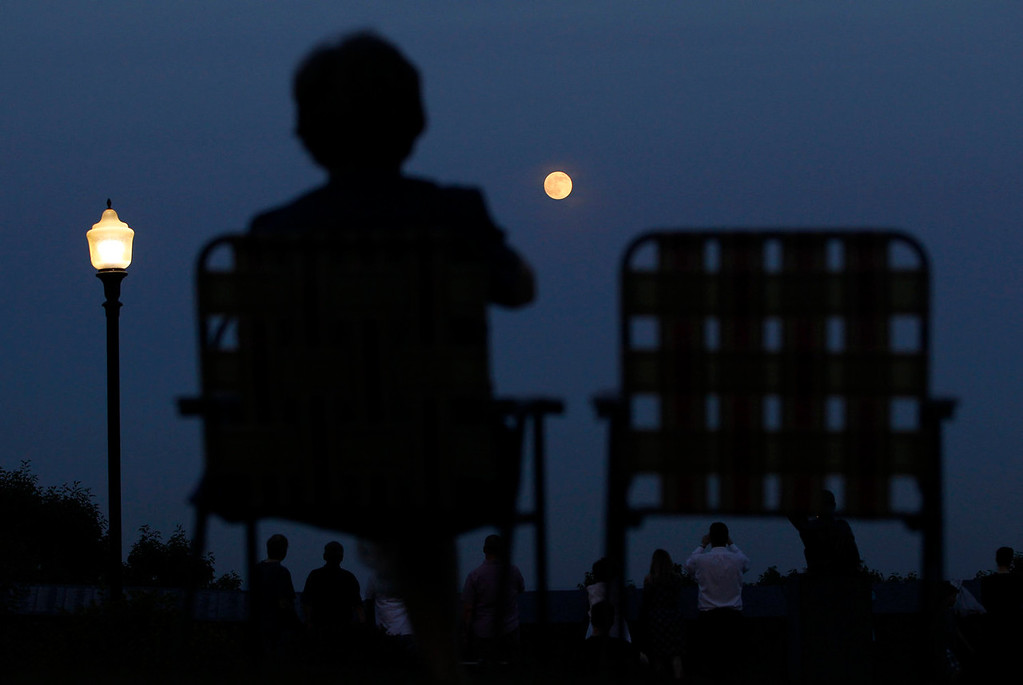". A women watches a full moon referred to as a ""super moon\"" rise in the sky from the Eagle Rock Reservation in West Orange, New Jersey on June 22, 2013. The largest full moon of the year called a \""super moon\"" will light up the night sky this weekend.  REUTERS/Gary Hershorn"