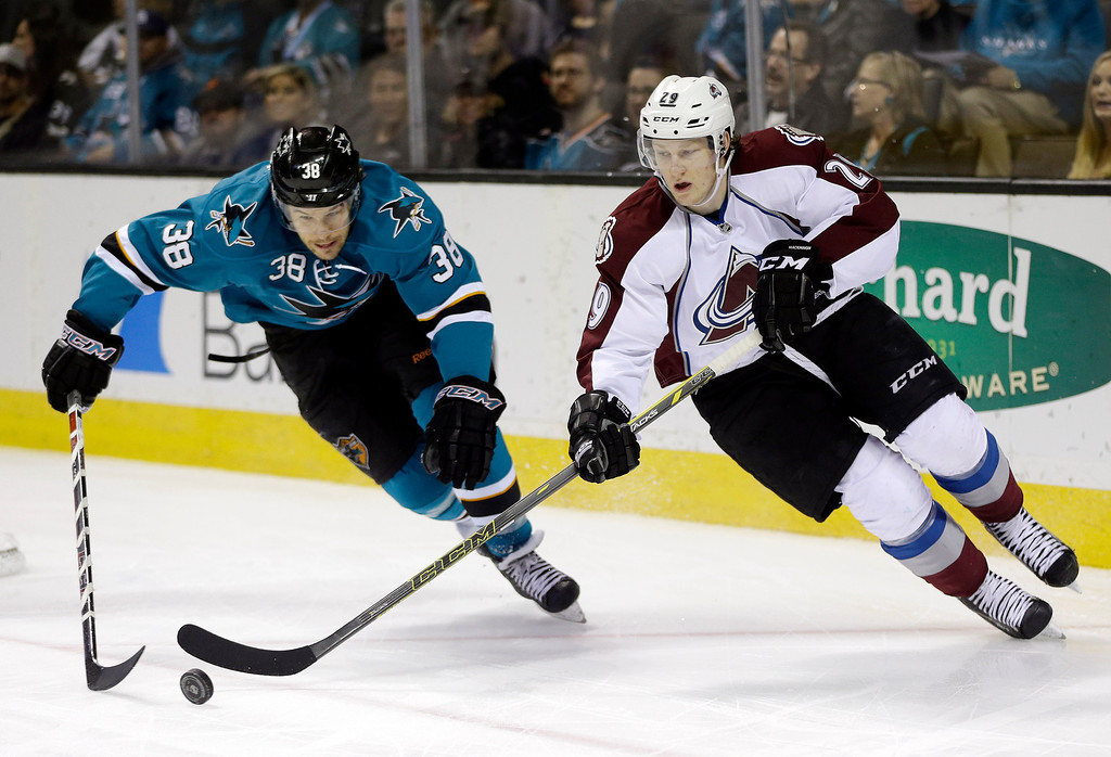 . Colorado Avalanche\'s Nathan MacKinnon, right, is chased by San Jose Sharks\' Bracken Kearns (38) during the first period of an NHL hockey game on Friday, April 11, 2014, in San Jose, Calif. (AP Photo/Marcio Jose Sanchez)