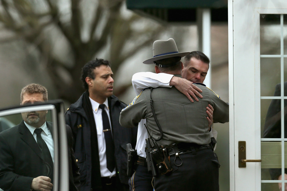 . Two law enforcement officers embrace as they arrive for the funeral services of six year-old Noah Pozner, who was  killed in the shooting massacre in Newtown, CT, at Abraham L. Green and Son Funeral Home on December 17, 2012 in Fairfield, Connecticut. Today is the first day of funerals for some of the twenty children and seven adults who were killed by 20-year-old Adam Lanza on December 14, 2012.  (Photo by Spencer Platt/Getty Images)