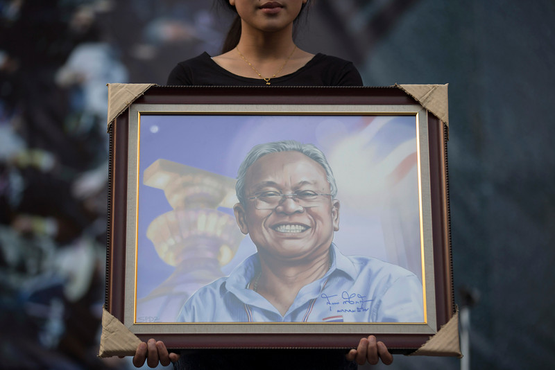 . Anti-government People\'s Democratic Reform Committee (PDRC) protester holds a portrait of Suthep Thaugsuban at an encampment in the Pathumwan district, Thursday, Jan. 16, 2014, in Bangkok. Anti-government protesters were on the march again in the Thai capital Thursday, targeting government offices they have not previous interfered with to keep up pressure on Prime Minister Yingluck Shinawatra to resign and call off next month\'s election. (AP Photo/John Minchillo)