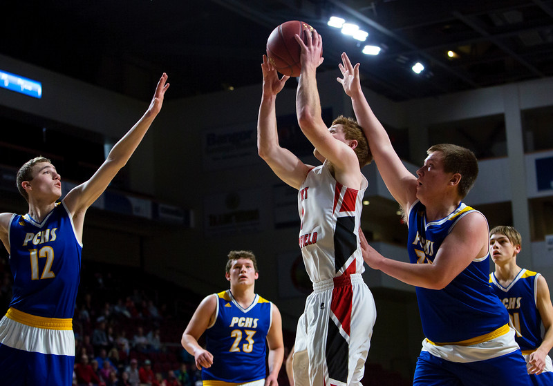 BANGOR, Maine -- 02/21/2017 -- Fort Fairfield's Ryan Player (center) puts up a shot past Piscataquis' Cameron Kane (left) and Piscataquis' Jarrod White during their Class C boys basketball quarterfinal game at the Cross Insurance Center in Bangor Tuesday. Ashley L. Conti | BDN