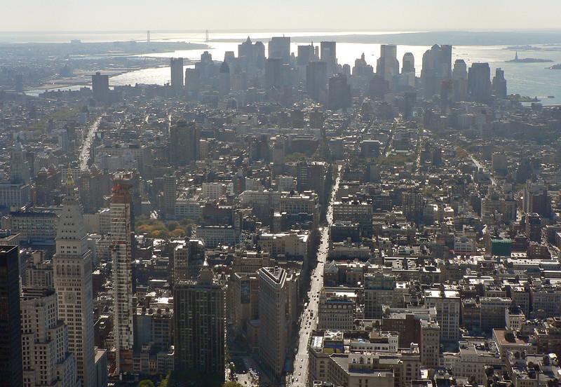 Vy mot södra delen av Manhattan. 5:e Avenyn går spikrakt medan Broadway ringlar sig som en orm genom stadsdjungeln. Verrazanobron i horisonten.