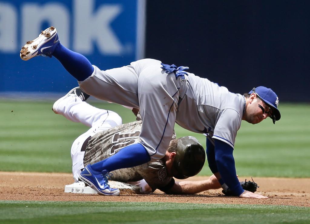 . Los Angeles Dodgers second baseman Nick Punto tumbles over San Diego Padres\' Logan Forsythe while relaying to first to complete a double play in the first inning of a baseball game in San Diego, Sunday, June 23, 2013. (AP Photo/Lenny Ignelzi)