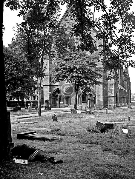 Govan churchyard, with man dormant. The headline on his paper reads 'JACKAL', so Carlos must have been in the news.   July 1975