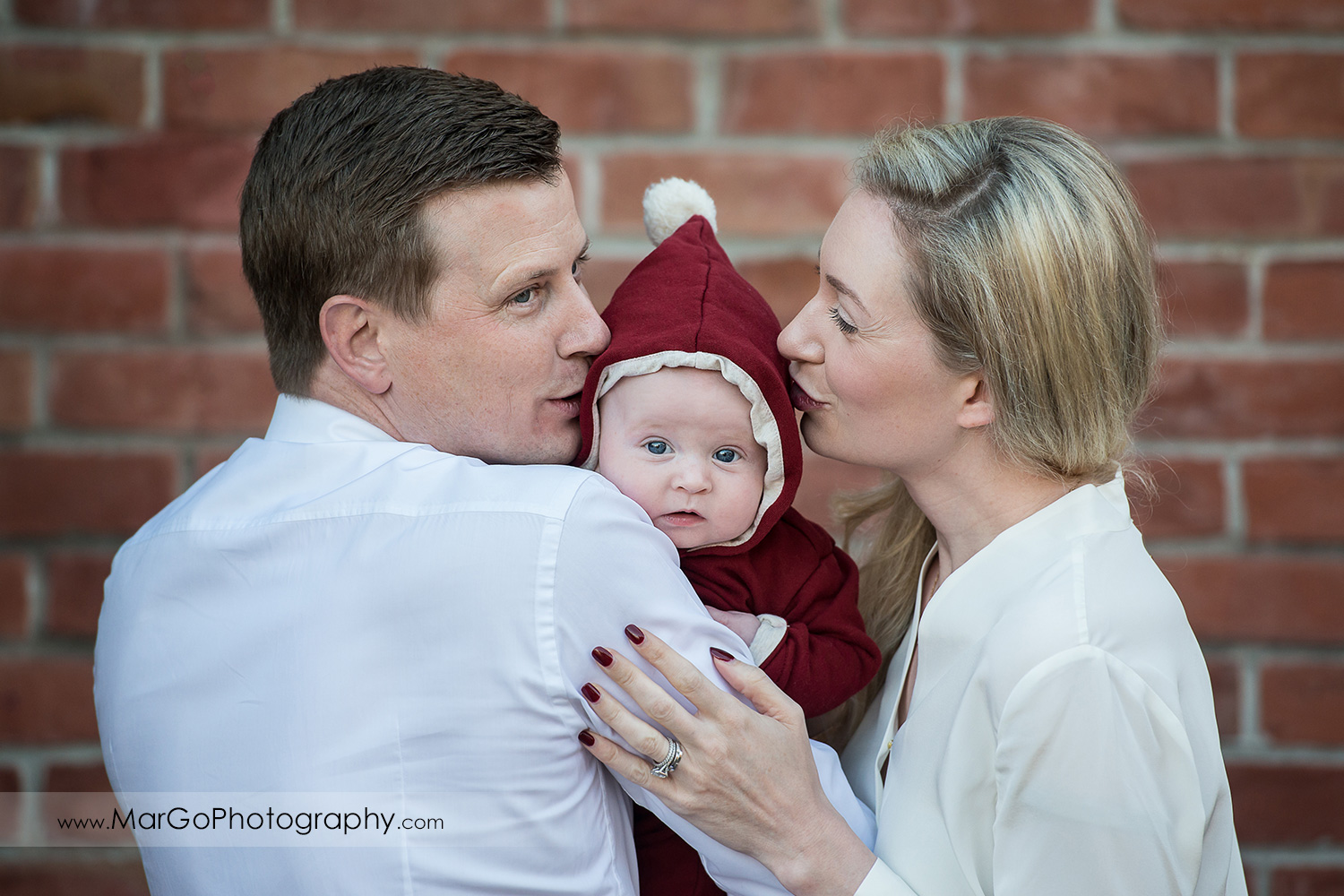 mother and father in white shirts kissing baby in Christmas jumpsuit on brick wall at San Francisco Ghirardelli Square