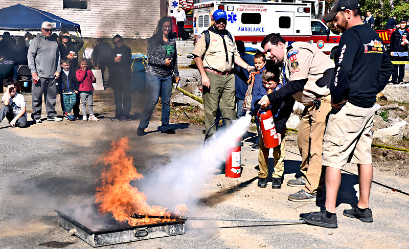 Putting out a fire at the Tyngsboro Fire Dept. open House is Joseph Lavallee 6 and his dad John Lavallee both from Dracut Cub Scout Den 3, under watchful eye of Stephen Roper with ASAP who conducted the demostration. SUN/David H.Brow