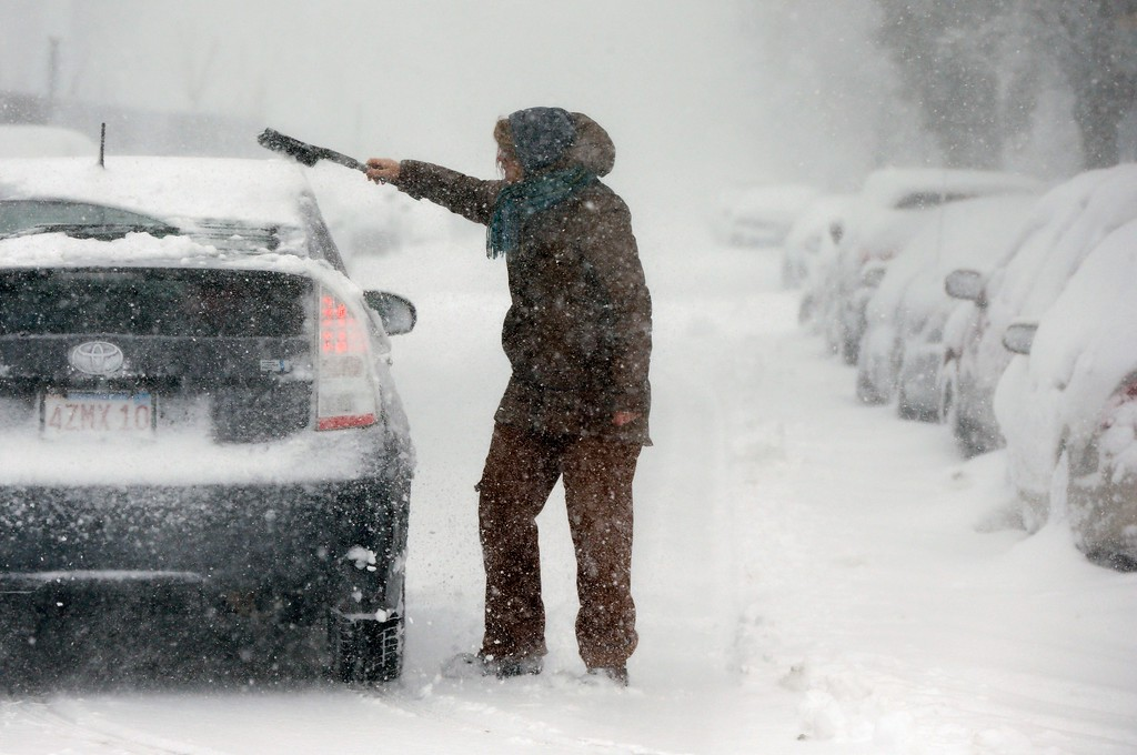 . A woman clears snow from a car on Marginal Street in Boston, Tuesday, March 13, 2018. Boston finds itself in the bullseye of the third nor\'easter in two weeks, with forecasters warning of up to 18 inches of snow and 2 feet or more to the south. (AP Photo/Michael Dwyer)