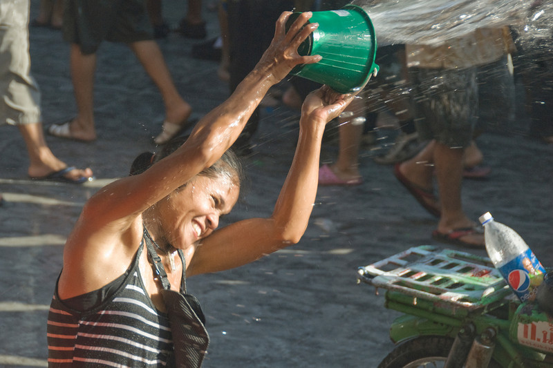Close-up shot of a woman throwing water from a bucket - Songkran Festival