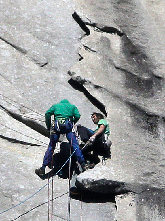 """. Tommy Caldwell, left, and Kevin Jorgeson near the summit of El Capitan Wednesday, Jan. 14, 2015, as seen from the valley floor in Yosemite National Park, Calif. The two climbers vying to become the first in the world to use only their hands and feet to scale a sheer granite face in California\'s Yosemite National Park are almost to the top. Jorgeson and Caldwell have been attempting what many thought impossible. The men have been \""""free-climbing\"""" to the 3,000-foot summit for 17 days, meaning they don\'t use climbing aids other than ropes only to prevent deadly falls. Each trained for more than five years, and they have battled bloodied fingers and unseasonably warm weather. (AP Photo/Ben Margot)"""
