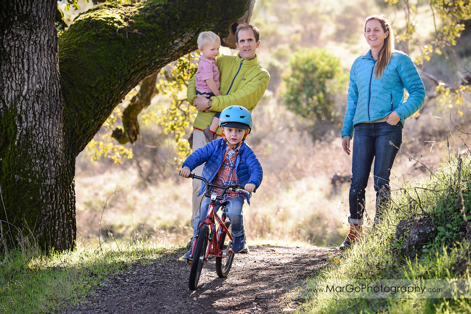 little boy in blue jacket riding a bike with parents in the background at San Raeael China Camp SP