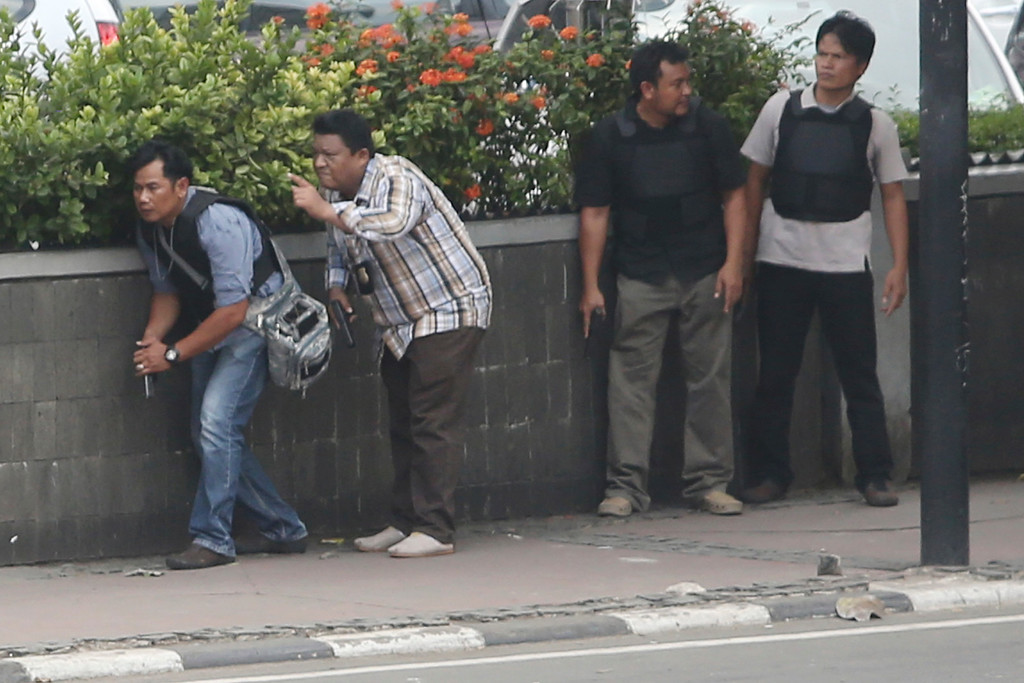 . Police officers take their positions as they search buildings near the site of an explosion in Jakarta, Indonesia Thursday, Jan. 14, 2016. Attackers set off explosions at a Starbucks cafe in a bustling shopping area of downtown Jakarta and waged gun-battles with police Thursday, leaving bodies in the streets as office workers watched in terror from high-rise windows. (AP Photo/Tatan Syuflana)