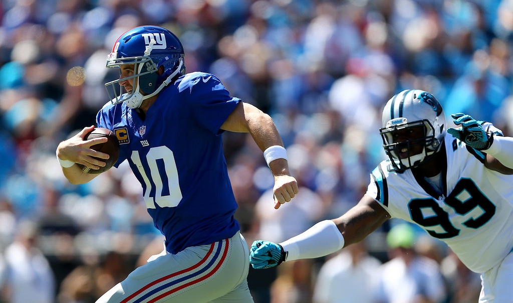 . Eli Manning #10 of the New York Giants tries to get away from Kawann Short #99 of the Carolina Panthers during their game at Bank of America Stadium on September 22, 2013 in Charlotte, North Carolina.  (Photo by Streeter Lecka/Getty Images)
