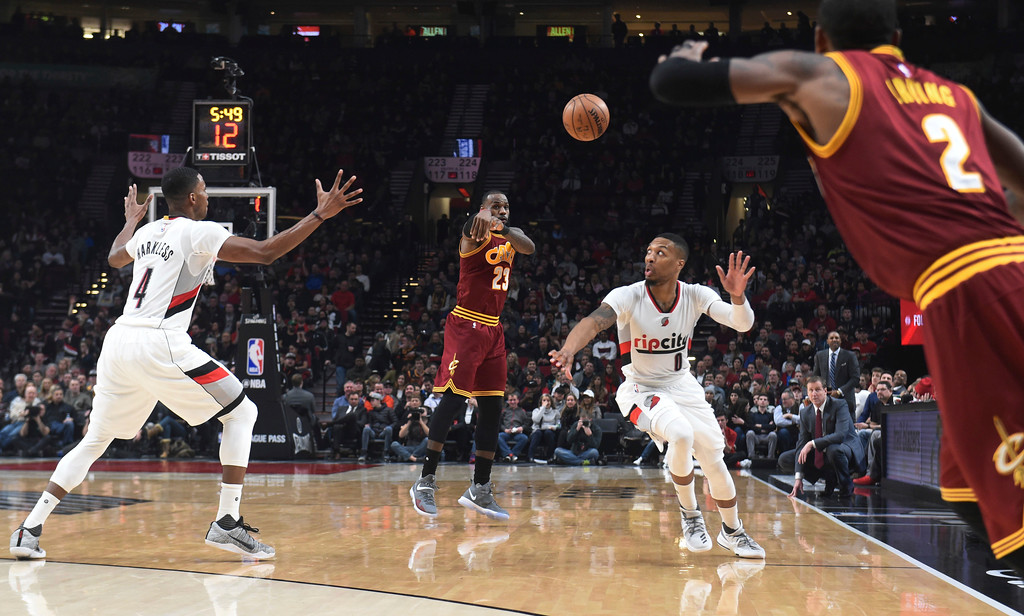 . Cleveland Cavaliers forward LeBron James passes the ball to guard Kyrie Irving as Portland Trail Blazers forward Maurice Harkless and guard Damian Lillard defend during the first half of an NBA basketball game in Portland, Ore., Wednesday, Jan. 11, 2017. (AP Photo/Steve Dykes)