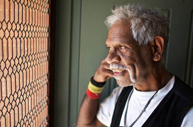 Aboriginal Man at his Front Door, Speaking on a Phone