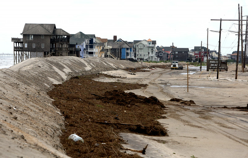 . The stretch heading north out of Mirlo Beach on Hatteras Island is covered with sand and seaweed after a storm, Friday, July 4, 2014, in Manteo, N.C. The storm was expected to bring a lousy July Fourth beach day with it as it moved offshore of the northeast coast. Forecasters did predict a second landfall Saturday evening in New Brunswick and Nova Scotia in Canada. (AP Photo/The Virginian-Pilot, Hyunsoo Leo Kim)