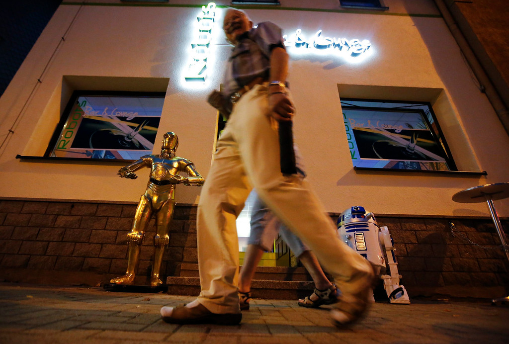 ". A pedestrian walks past the Robots Bar and Lounge where humanoid robot bartender ""Carl\"" is helping to serve customers, in the eastern German town of Ilmenau, July 26, 2013. \""Carl\"", developed and built by mechatronics engineer Ben Schaefer who runs a company for humanoid robots, prepares spirits for the mixing of cocktails and is able to interact with customers in small conversations. Picture taken July 26, 2013. REUTERS/Fabrizio Bensch"