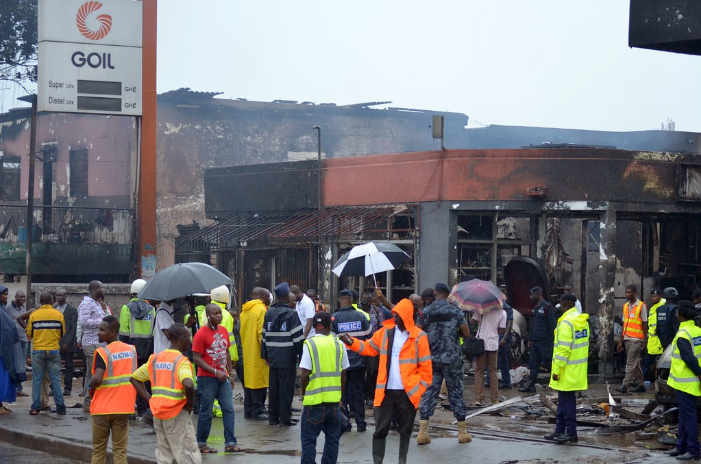 . Rescuers and officials stand in front of the burnt-out petrol station where over 90 people were killed in a fire in Accra, on June 4, 2015. The fire broke out at the filling station in the Kwame Nkrumah Circle area of the city late on Wednesday night and is thought to have spread from a nearby residence. AFP PHOTO /  FATI BRAIMAH/AFP/Getty Images