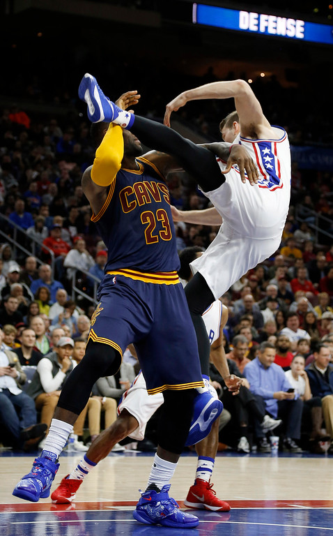 . Cleveland Cavaliers\' LeBron James, left, and Philadelphia 76ers\' Nik Stauskas collide while chasing a rebound during the first half of an NBA basketball game, Sunday, Jan. 10, 2016, in Philadelphia. (AP Photo/Matt Slocum)