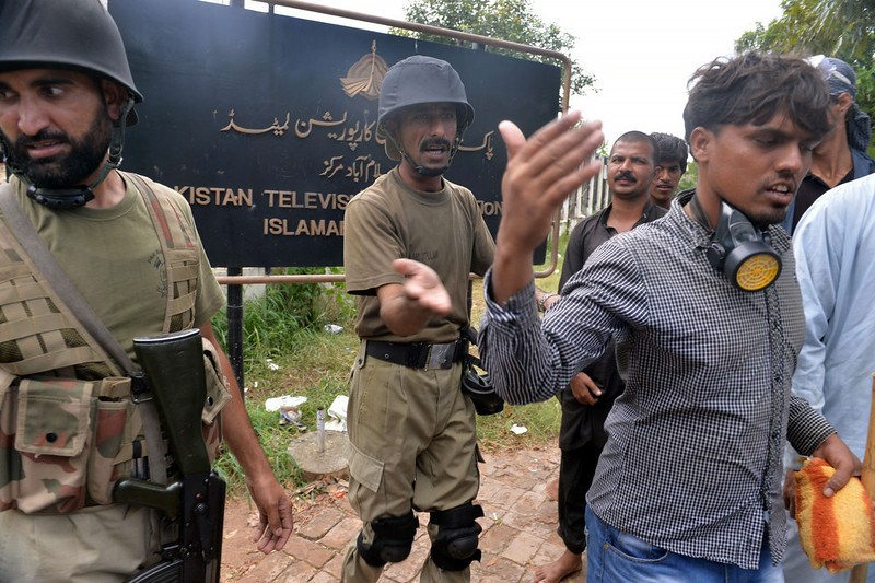 . Pakistani soldiers move supporters of Canadian cleric Tahir ul Qadri and cricket-turned politician Imran Khan on after demonstrators stormed the headquarters of the state-owned Pakistani Television (PTV) during anti-government protests in Islamabad on September 1, 2014. Hundreds of protesters trying to topple Pakistan\'s government stormed the state broadcaster on September 1 as fresh clashes with police broke out in Islamabad. AAMIR QURESHI/AFP/Getty Images