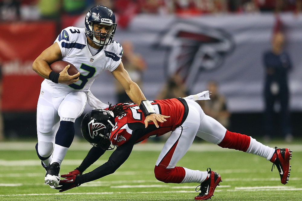. Russell Wilson #3 of the Seattle Seahawks tries to avoid the tackle of  Jacquizz Rodgers #32 of the Atlanta Falcons in the first quarter during the NFC Divisional Playoff Game at Georgia Dome on January 13, 2013 in Atlanta, Georgia.  (Photo by Mike Ehrmann/Getty Images)