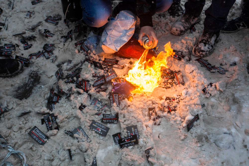 . In this photo taken on Friday, March 15, 2013, members of a pro-Kremlin youth group burn plastic bags with spice, a synthetic drug, along with business cards that belong to spice pushers, in Moscow, Russia. Russian officials and anti-drugs campaigners say that spice has become one of the most dangerous drugs widely available to youngsters and almost impossible to ban because of the constantly changing chemical ingredients. (AP Photo/Alexander Zemlianichenko Jr)