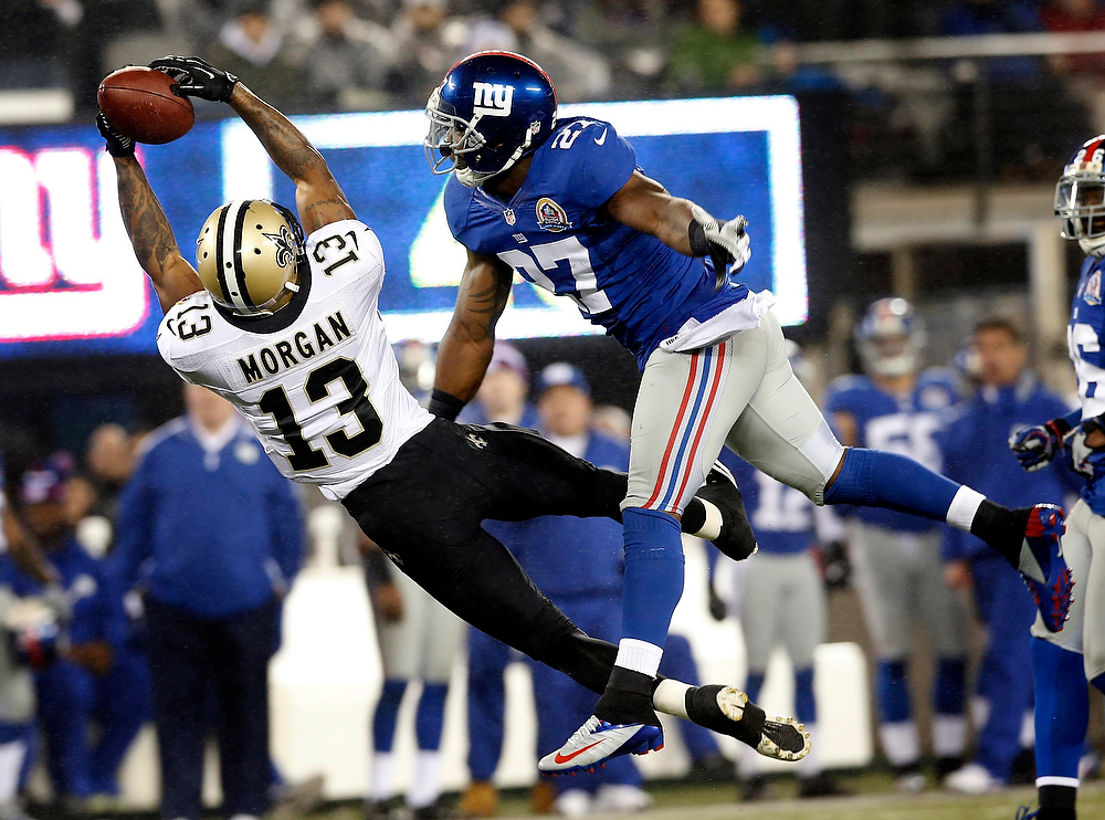 . New Orleans Saints wide receiver Joseph Morgan (L) makes a leaping catch past New York Giants\' defender Stevie Brown (R) in the fourth quarter of their NFL football game in East Rutherford, New Jersey, December 9, 2012. REUTERS/Mike Segar