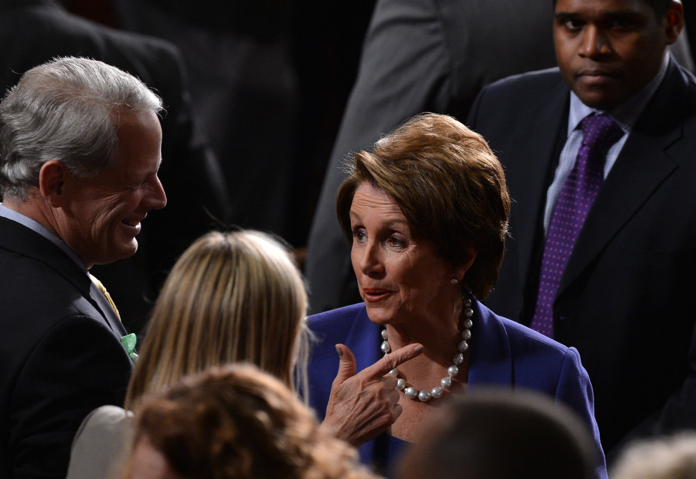 . House Minority Leader Nancy Pelosi (C), D-CA, confers on the House floor prior to US President Barack Obama\'s State of the Union address before a joint session of Congress on February 12, 2013 on Capitol Hill in Washington, DC. JEWEL SAMAD/AFP/Getty Images