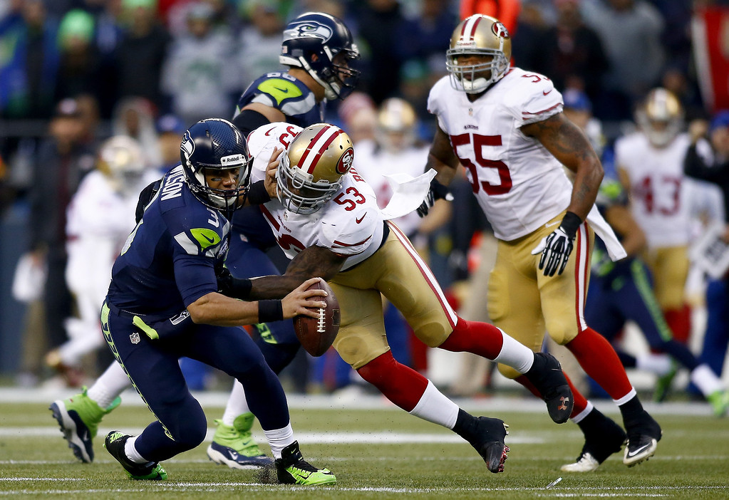 . Quarterback Russell Wilson #3 of the Seattle Seahawks is hit by inside linebacker NaVorro Bowman #53 of the San Francisco 49ers in the first half during the 2014 NFC Championship at CenturyLink Field on January 19, 2014 in Seattle, Washington.  (Photo by Jonathan Ferrey/Getty Images)