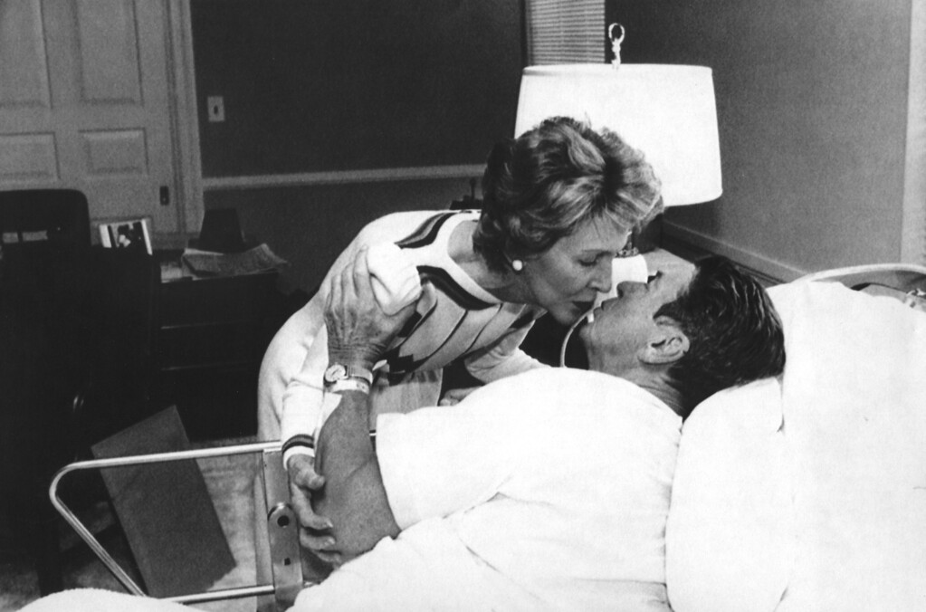 . (07/14/85-Bethesda, MD) Hospital Kiss-First Lady Nancy Reagan greets President Ronald Reagan in his hospital bed at Bethesda Naval Hospital on Sunday morning. President Reagan underwent surgery to remove an intestinal polyp on Saturday.(AP Photo/Bill Fitz-Patrick)