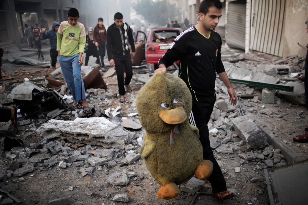 Description of . A Palestinian man carries a stuffed toy in a street littered with debris after a Israeli air raid on a nearby sporting centre in Gaza City on November 19, 2012.  Israeli air strikes on Sunday killed 31 Palestinians in the bloodiest day so far of its air campaign on the Gaza Strip, as diplomatic efforts to broker a truce intensified.   MARCO LONGARI/AFP/Getty Images