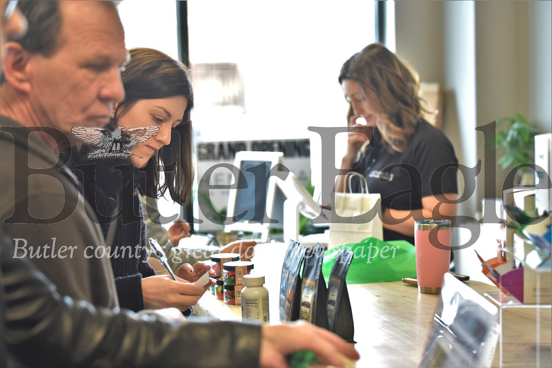 Mackenzie Baldinger looks at a selection of CBD products while waiting to check out at the grand opening of Hemporia in the Shoppes at Adams Ridge in Mars Saturday. Seb Foltz/Butler