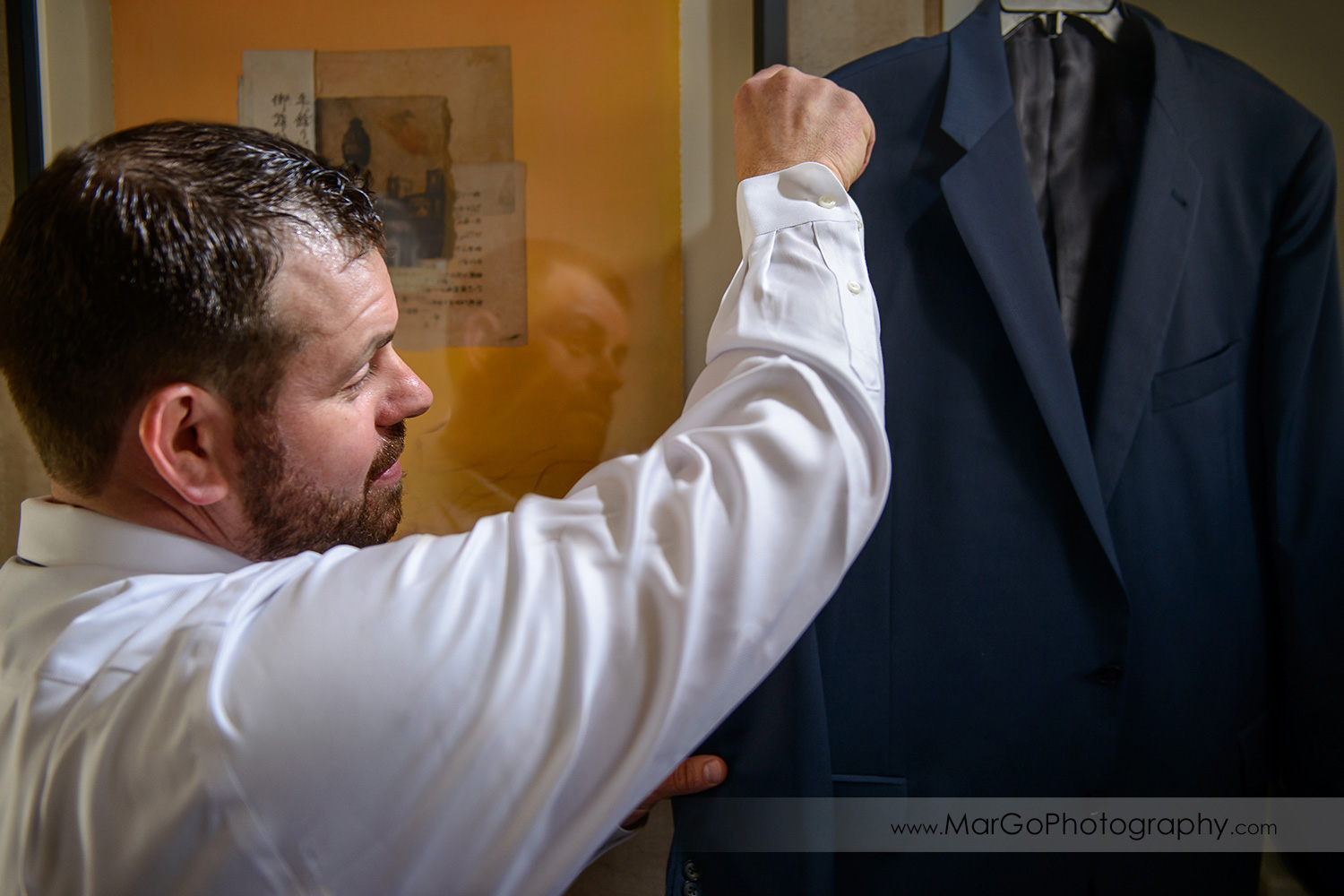 groom reaching for a navy blue jacket during wedding preparation at Los Gatos Lodge
